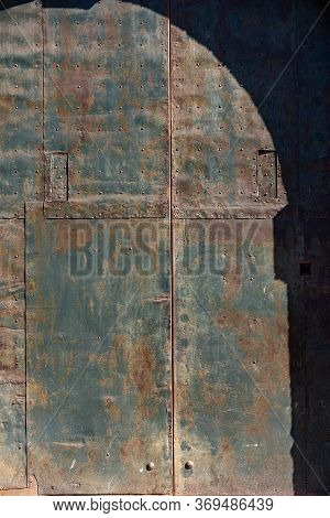 Closeup Of An Ancient Wrought Iron Door With Studs And Rust. Full Frame, Background. Trento, Trentin
