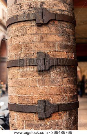 Closeup Of An Ancient Brick Column Reinforced With Wrought Iron Belts, Danger Of Collapse, Bologna D