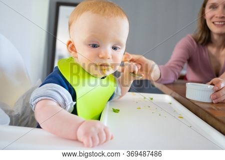 Cheerful Mom Feeding Baby Daughter With Spoon. Little Child In Plastic Bib With Food On Face, Eating