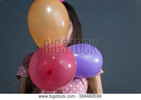 Girl Hiding Behind Colorful Balloons, Depressed. Studio Photo On A Gray Background. Depressive Psych