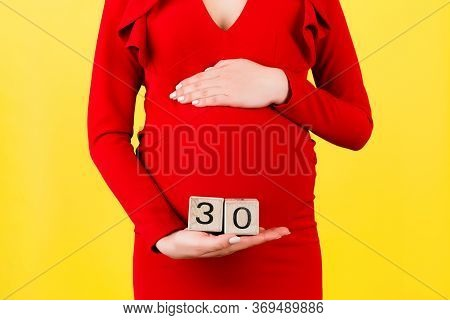 Close Up Of Pregnant Woman In Red Dress Holding Cubes With Numbers Of Pregnancy Weeks. Thirty Weeks