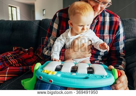 Grandpa Showing Toy To Baby Girl At Home. Little Child Sitting On Senior Mans Lap And Playing Learni