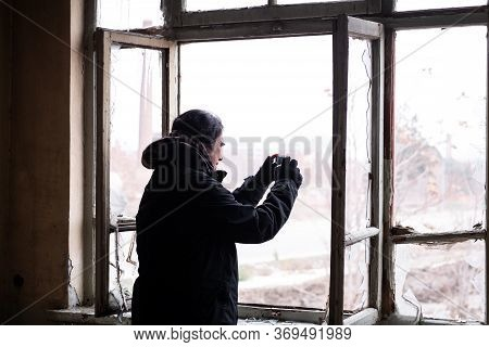 Adult Man With Black Cold Winter Coat Taking Pictures Of The Outside View From The Broken Window Of