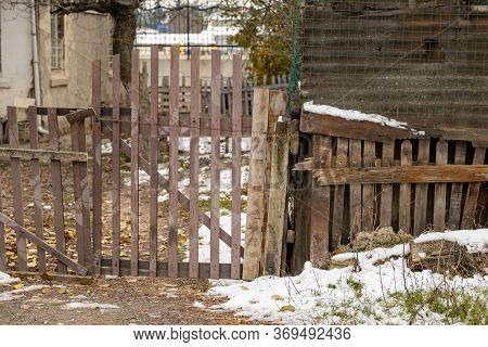 Wiew Of A Wooden Fence Door Of A Garden On A Cold Winter Day. Abandoned And Derelict Building In A D