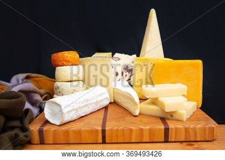 Tasty Different Cheeses Laying On Wooden Board. Healthy Traditional Delicatessen. Studio Shot. Side