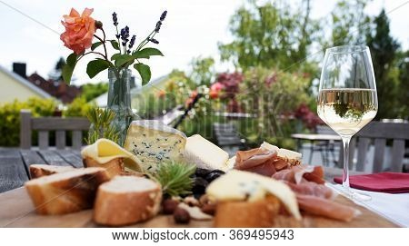 Antipasto With Glass Of White Wine On A Garden Terrace. Summerly Food Photography With Short Depth O