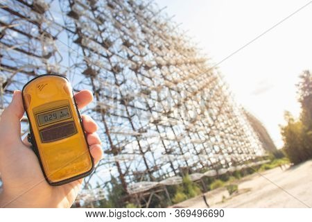 Hand Holding A Yellow Dosimeter Indicating Radiation On The Screen. Enormous Duga Radar Complex Seen