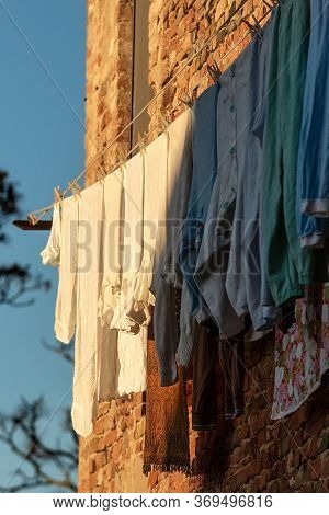 Group Of Clothes Hanging Outside The Window On A Clothesline To Dry In The Sun. Certaldo Village, Tu
