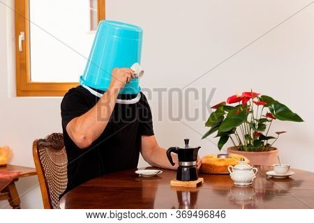 Man drinks coffee with a blue bucket on his head, flowers in the background and the coffee maker on the table