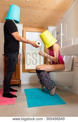 Man with bucket on his head passes the toilet paper to his wife sitting on the toilet, she too with bucket on her head. Funny situation.