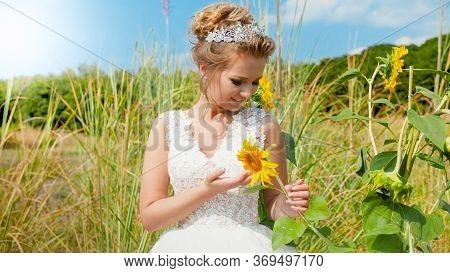 Portrait Of Beautiful Elegant Newly Married Bride Holding Sunflower On Field