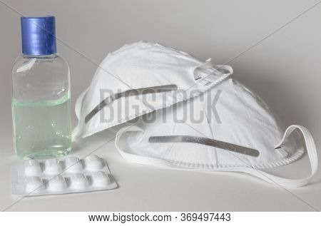 Hand Sanitiser, Medicine And Two Face Masks Isolated On A White Background