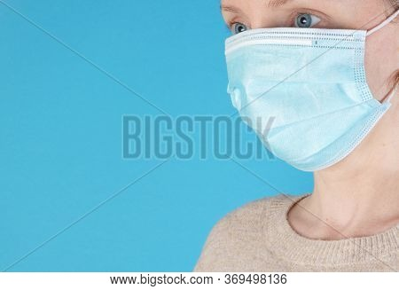 Woman Wearing A Blue Face Mask, Isolated Against A Bright Blue Background