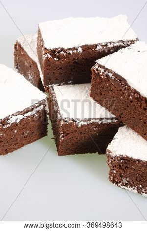 A Studio Photograph Of Chocolate Brownies Against A White Background
