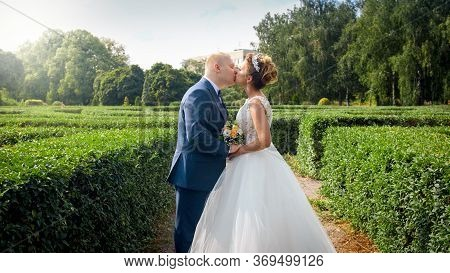 Portrait Of Elegant Newly Married Couple Kissing In Park Or Garden