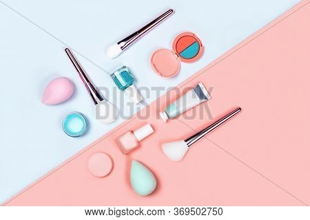 Makeup Products With Brushes, Nail Polish, Sponges, Eyeshadow, Cream And Lipstick On Coral-blue Colo