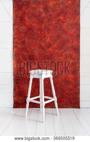 White High Wooden Stool With A Red Textured Background. Bar Chair In White Wooden Minimalist Room. S