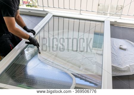 A Professional Window Cleaner Using A Window Cleaner Squeegee To Clean A Large Fold Down Apartment W