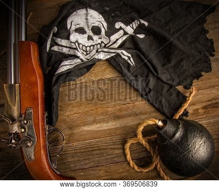 Classic Round Black Antique Bomb With A Long Rope Wick And A Pirate Flag Jolly Roger On A Rough Wood