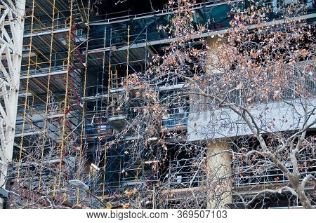 Construction Scaffolding Of High-rise Building And Dried Leaves Tree In Autumn