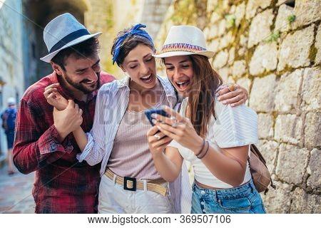 Happy Friends Enjoying Sightseeing Tour In The City, Having Fun, Using Phone.