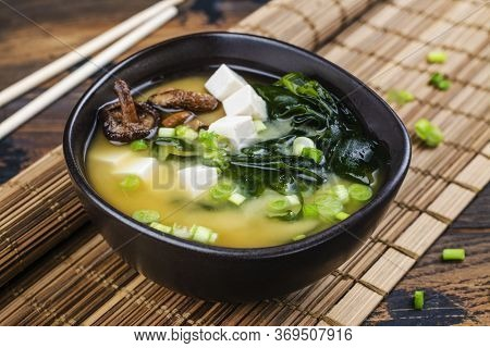 Traditional Miso Soup With Wakame Seaweeds, Tofu And Shiitake Mushrooms On Bamboo Mat. Copy Space