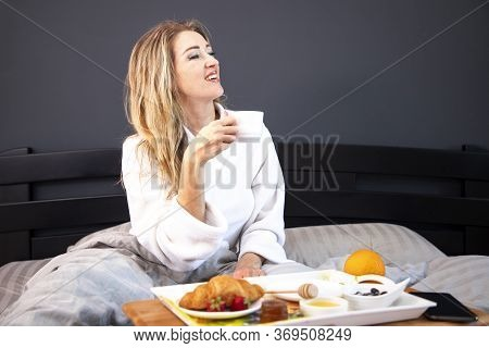 Breakfast In Bed. Young Woman Eating Breakfast In Bed. Beautiful Young Woman Smiling.