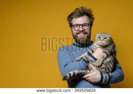 Funny Smiling Shaggy Man Hugs His Adorable Cat, Who Is Not Happy That The Owner Is Holding It In Han