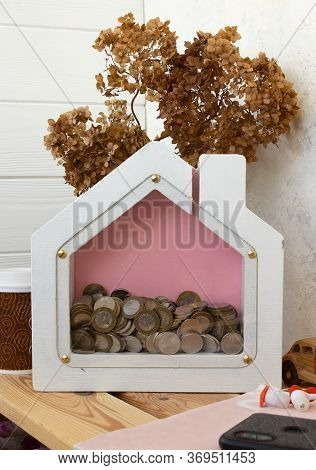 The Concept Of Money, Accumulation. Piggy Bank In The Form Of A House On A Shelf Of The House. Cash