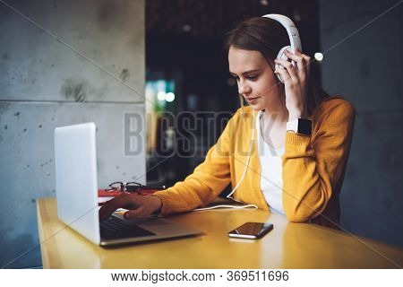 Young Woman Updating Playlist On Media Application