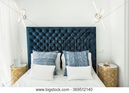 Fragment Of Modern Master Bedroom In Minimalist White And Blue Interior Design Style. Bed With Pillo