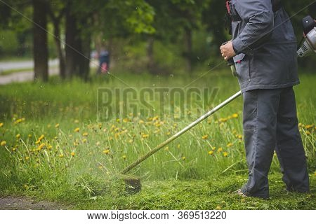 A Worker In Gray Protective Clothing With A Lawnmower In His Hands Mows Grass Next To The Road And T