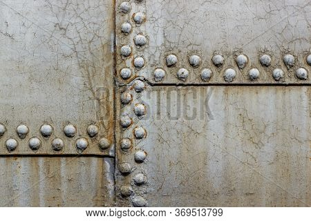 Rusty Rivets On Iron Armor. Abstract Background Of Grunge Metal Sheet With Rivets. Steel Wall Mats S
