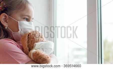 A Little Child Girl In A Mask With A Dog Toy Looking Out The Window. Covid-19 Concept