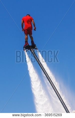 Fly Board, Man On A Flyboard In Red. Water Extreme Sport. The Guy Is Flying At The Aquatic Flyboard.