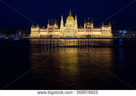 Illuminated Budapest Parliament Building At Night With Dark Sky And Reflection In Danube River, Hung