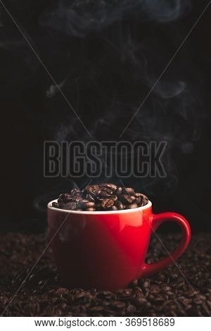 Red Cup With Smoking And Steaming Coffee Beans On Table Covered With Coffee Beans.coffe Themed Backg