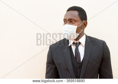Portrait Of African Businessman With Mask Thinking Against White Background
