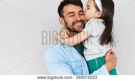 Indoor Image Of Happy Father Smiling Broadly Hold Embrace His Cute Daughter Kissing On The Cheek. Lo