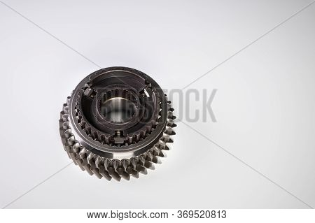 A New Gear Part On A Gray Background. The Concept Of New Parts And Spare Parts