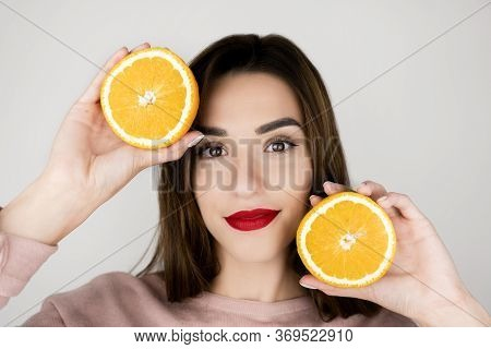 Portrait Of Young Brunette Woman With Red Lips Holding One Half Of Orange In One Hand And Another Ha