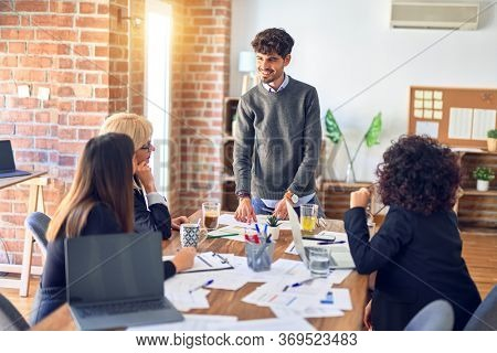 Group of business workers smiling happy and confident. Working together with smile on face. Young handsome man standing explaining documents at the office