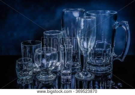 Glass Drinkwares And Stemwares Of Different Shapes And Sizes Stand Side By Side On An Isolated Black