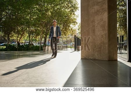 Stylish Young Businessman Walking To Work During His Morning Commute