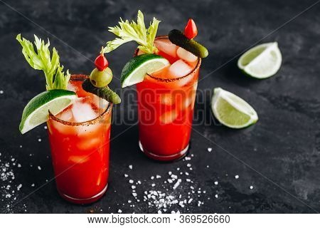 Bloody Mary Cocktail In Glasses With Garnishes. Tomato Bloody Mary Ice Cold Drink With Fresh Celery,