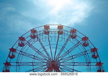 A Distant View Of A The Top Half Of A Symmetrical, Vintage Ferris Wheel At A Seaside Fairground With