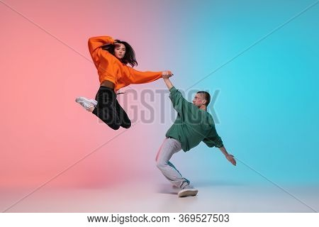 In Jump. Boy And Girl Dancing Hip-hop In Stylish Clothes On Colorful Gradient Background At Dance Ha