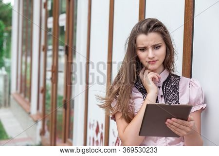 Shocking News. Closeup Portrait Shocked Girl Looking At Pad Reading Bad News. Young Funny Woman Star