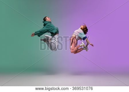 High Jump. Boy And Girl Dancing Hip-hop In Stylish Clothes On Colorful Gradient Background At Dance