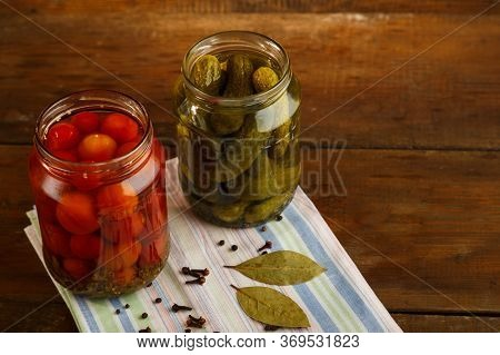 Jars Of Pickled Cucumbers And Cherry Tomatoes Homemade Pickling On A Linen Towel On A Wooden Table.